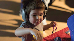 Child wearing headphones plays at the Audubon Nature Institute