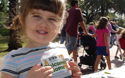 "A little girl smiles and holds a piece of paper that says ""Welcome Home""."