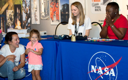 2 women sit behind a table covered in a blue tablecloth with NASA written on it while a mother and child stand nearby.