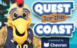 Image of the New Orleans Pelicans mascot posing in front of a sign for Quest for the Coast presented by Chevron.