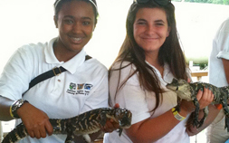 2 Jr Zookeepers smile as they hold small alligators.