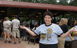 A woman wearing a Saints themed shirt poses for the camera while attending a Game Night Tailgate party at Audubon Zoo's Picnic Pavilion.