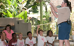 A small group of children watch an animal presentation at Audubon Zoo's Shell's Wildlife On Stage!
