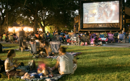 Families sit in the grass at night while watching a movie on big screen at Audubon Zoo.