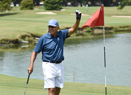 A male golfer in a blue shirt and white shorts holds a golf ball in the air celebrating while golfing at the Golf Club at Audubon Park in New Orleans.