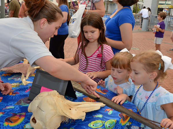 Youth volunteers show a family different aquatic items as part of the Aquavan outreach program.
