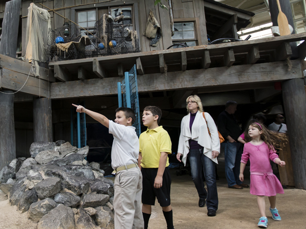 A lady and 3 kids explore the Mississippi River exhibit at the Audubon Aquarium of the Americas.