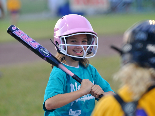 A little girl in a green shirt and pink baseball helmet smiles as she holds a baseball bat.