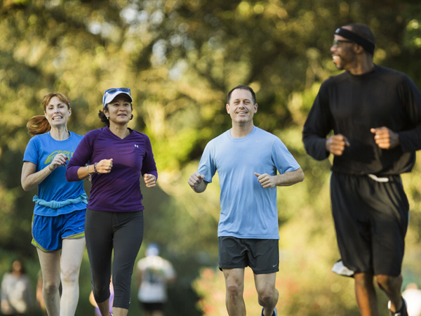 4 people jog along the Audubon Park jogging path in New Orleans.