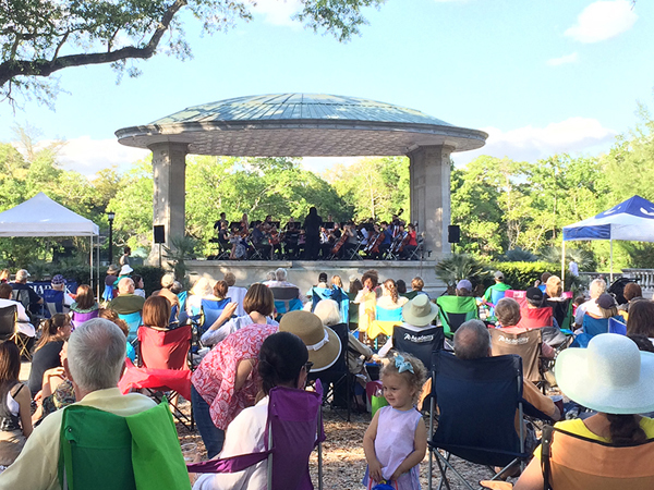 A large group of people gather to listen to the Music Under the Oaks concert series held at Newman Bandstand in Audubon Park.