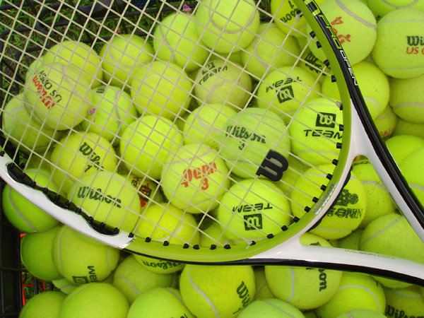 A tennis racket hovers over a large pile of yellow tennis balls.