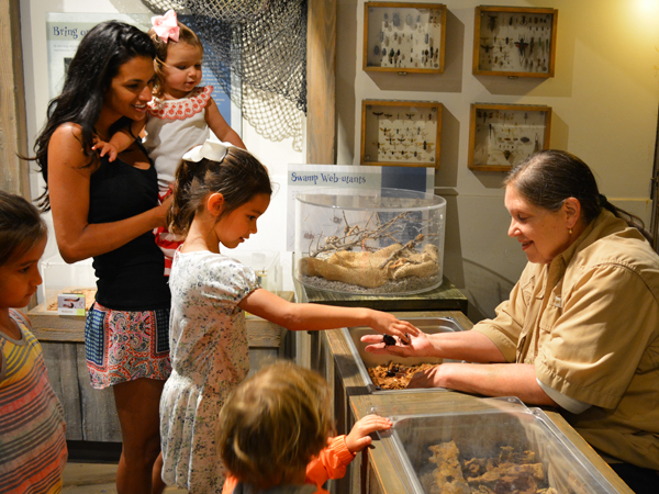 An Audubon Nature Institute educator shows a group of children one of our hands-on nature learning experiences.