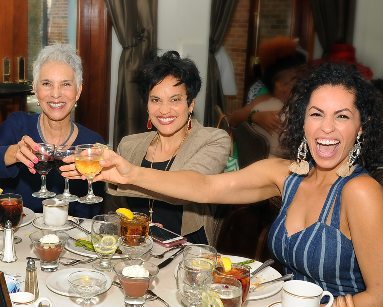 3 ladies raise wine glasses and toast while attending Audubon Zoo's Mother's Day event.