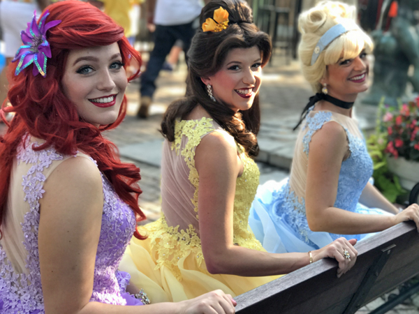 The musical trio, The Pop Princesses featuring Ariel, Belle and Cinderella, sit on a bench looking over their shoulders.