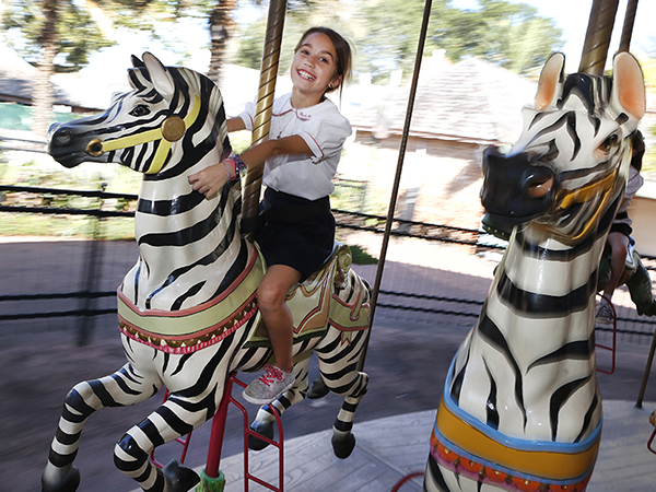 Children ride the Gottesman Family Endangered Species Carousel at Audubon Zoo.