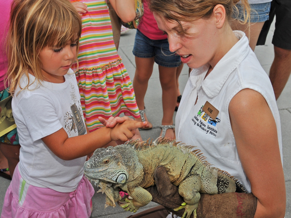 An Audubon Nature Institute Animal Ambassador shows an iguana to a group of children.